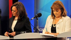 Kamala Harris and Loretta Sanchez in polar opposite pearls and attire, keep notes during debate. Photo by Ken Stone