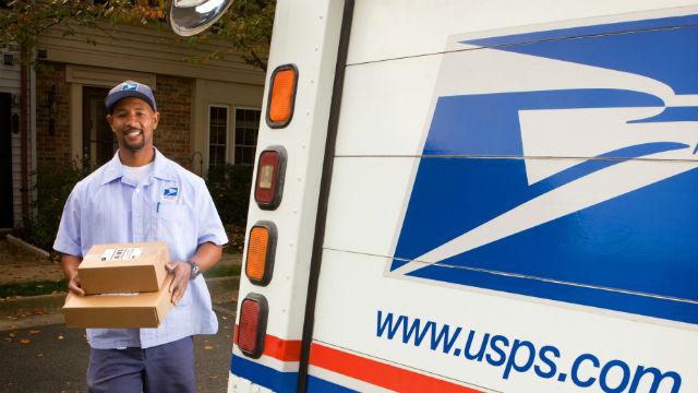A letter carrier delivering mail. Courtesy USPS