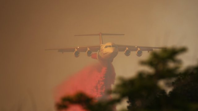 A tanker drops retardant on the Border Fire north of Tecate. Photo by Kevin Pack / Cal Fire