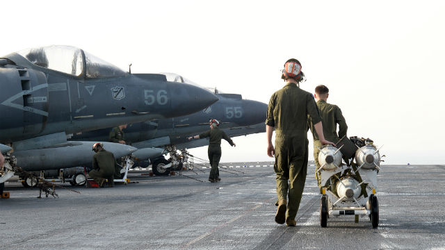 Marines aboard the USS Boxer prepare to load bombs onto an AV-8B Harrier II jet. Navy photo