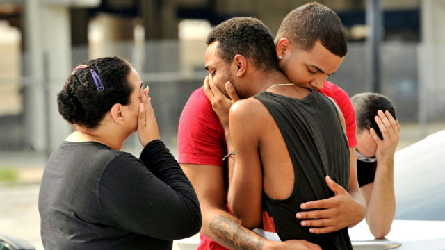 Friends and family members embrace outside the Orlando Police Headquarters during the investigation of a shooting at the Pulse night club, where 50 people were killed. REUTERS/Steve Nesius