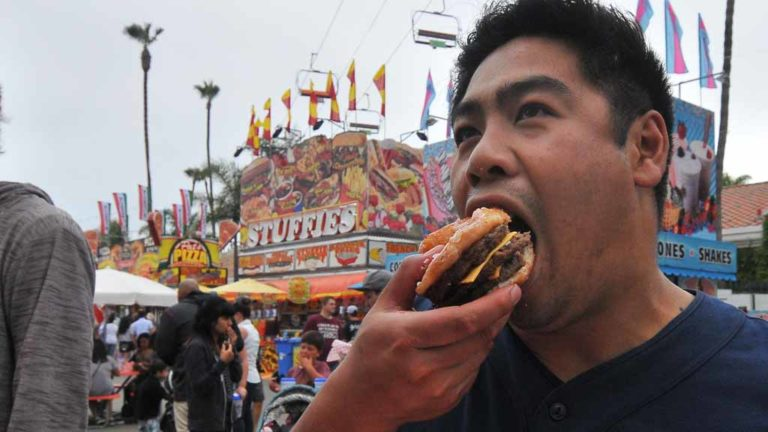 Alexander Fune of San Diego enjoys one of his favorite food's, triple Crispy Kreme burger from Chicken Charlie's. Photo by Chris Stone