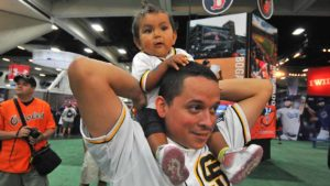 Peter Hernandez with his 10-month-old daughter, Marisol, watch activities at Fan Fest.  Photo by Chris Stone