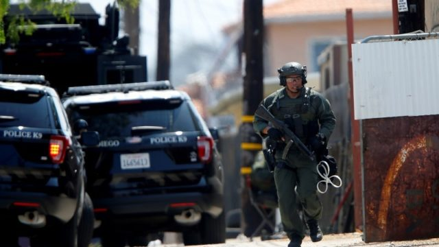 A SWAT officer runs down a back alley as police surround a home after a San Diego police officer was fatally shot and another was wounded on Thursday. REUTERS/Mike Blake