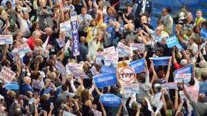 Bernie Sanders signs show support for defeated Democrat on the floor of the convention. Photo by Chris Stone