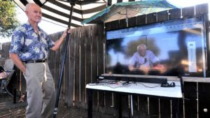 David Burnight of Crest briefly held a patio umbrella to shade TV screen. Photo by Ken Stone