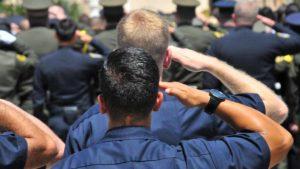Police salute during outside ceremonies for slain Officer Jonathan De Guzman in El Cajon. Photo by Chris Stone