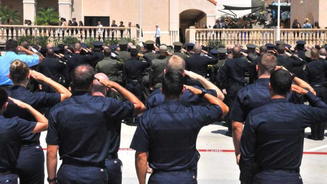 Thousands of law enforcement officers salute during outside ceremonies for slain Officer Jonathan De Guzman in El Cajon. Photo by Chris Stone