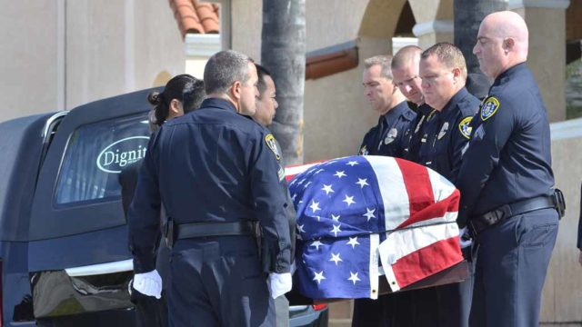 Pallbearers remove the casket carrying officer Jonathan De Guzman before the memorial ceremony. Photo by Chris Stone