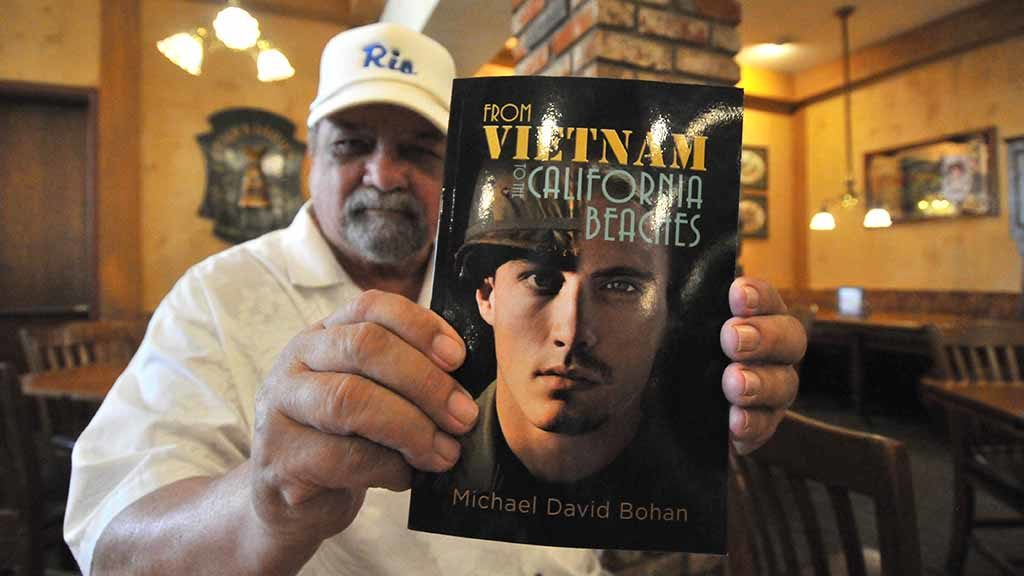 "Mike Bohan holds ""From Vietnam to the California Beaches."" Photo by Ken Stone"