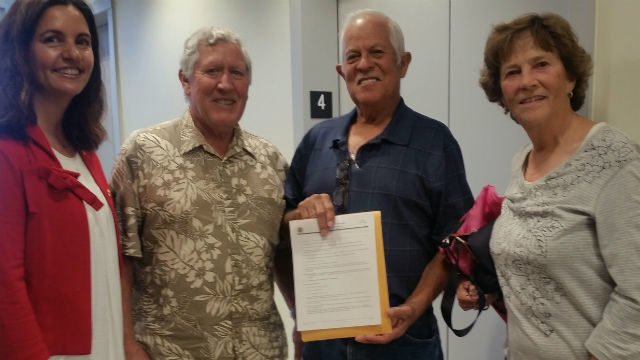 New American Urbano Chavarrin holds his citizenship papers as Executive Director Linda Martinez Haley (left), founding member Steve Carlton and volunteer tutor Mary Diaz look on.