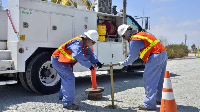 SDG&E workers show how they close a natural gas shut-off valve when gas is reported. Photo by Chris Stone