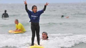 A youth at Surf with a Cop Day at La Jolla Shores celebrates her newfound surfing talent. Photo by Chris Stone