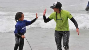 Volunteer Kristina Estes high fives her partner after a successful surf. Photo by Chris Stone