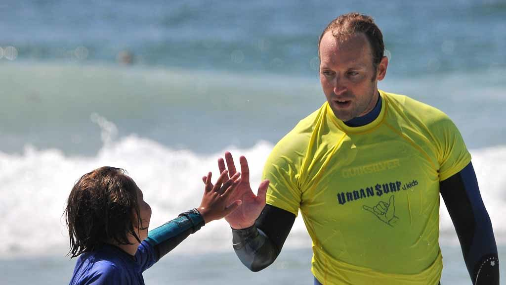 Gavin Lanning, of the San Diego County Sheriffs Department, congratulates a young surfer on making it to shore on the board. Photo by Chris Stone