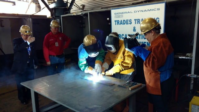 """Hershel """"Woody"""" Williams shields his eyes as his daughters Travie Ross and Tracie Ross practice welding at NASSCO. Photo by Chris Jennewein"""
