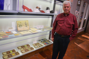 San Diego History Center Executive Director Bill Lawrence poses by a current exhibit that perhaps could be used in the upcoming Jewish exhibition: labels of canned foods packaged and distributed in the early 20th century by the Jewish-owned Klauber Wangenheim Co. Photo via San Diego Jewish World