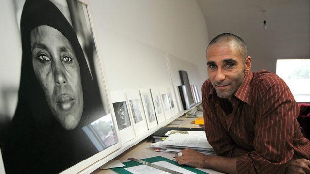 Fazal Sheikh with one of his portraits. Courtesy John D. and Catherine T. MacArthur Foundation via Wikimedia Commons