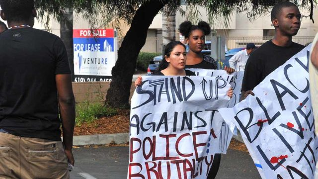 Protesters bring signs to site of police shooting in El Cajon. Photo by Chris Stone