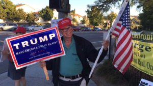 Sean Colgan holds sign and flag at recurring Trump rallies at Oceanside Boulevard and state Route 76. Photo via Facebook