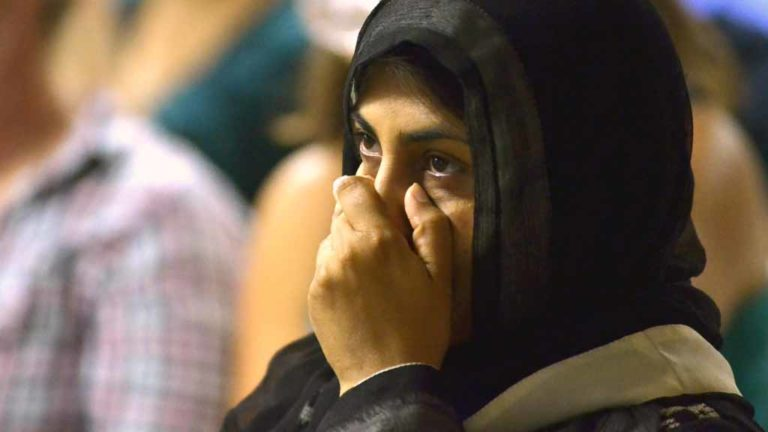 At Islamic Center of San Diego, a woman listens intently as Donald Trump speaks during third debate. Photo by Chris Stone