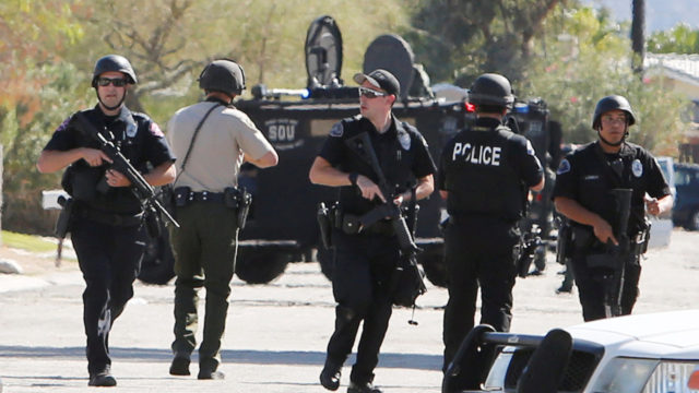 Armed police officers in Palm Springs after a gang memer shot three officers, killing two. REUTERS/Sam Mircovich