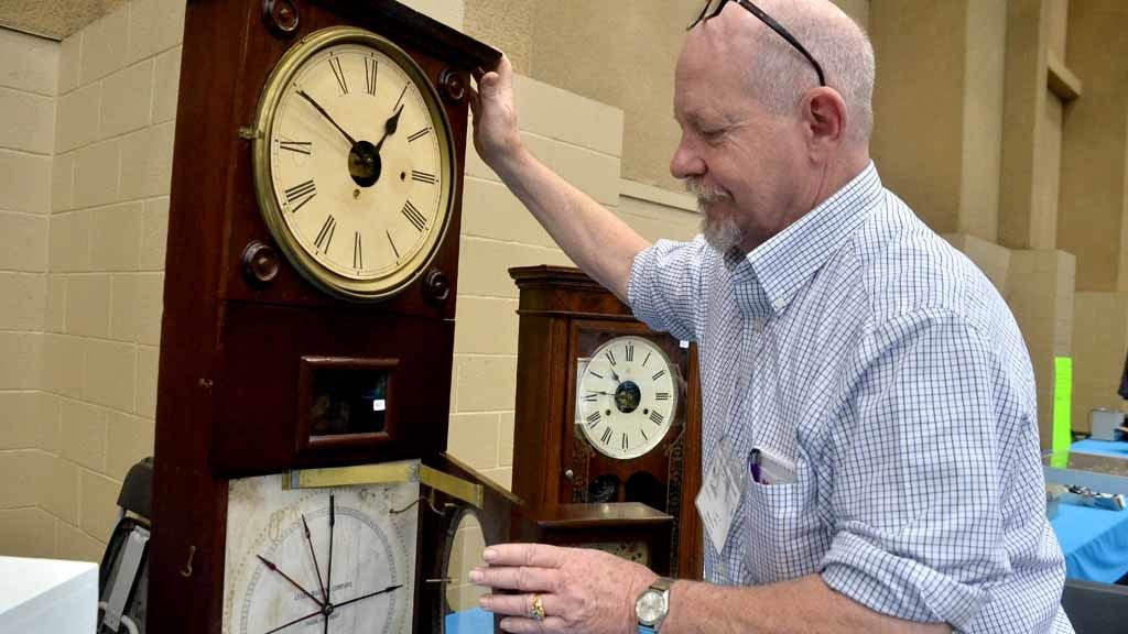 Nile Godfrey, who owns a clock shop in Livermore, shows off his latest acquisition at the Southwest California regional National Association of Watch & Clock Collectors convention at the Del Mar Fairgrounds. Photo by Chris Stone