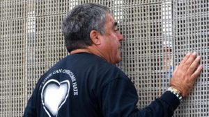 Enrique Morones, founder and director of Border Angels speaks with Mexican citizens through the fence. Photo by Chris Stone