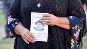 Mourners carried programs at Chunky Sánchez memorial service in Chicano Park. Photo by Chris Stone