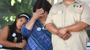 Family members react at Chunky Sánchez memorial service in Chicano Park. Photo by Chris Stone