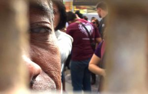 A Mexican man looks through the border fence after the family visitations. Photo by Chris Stone
