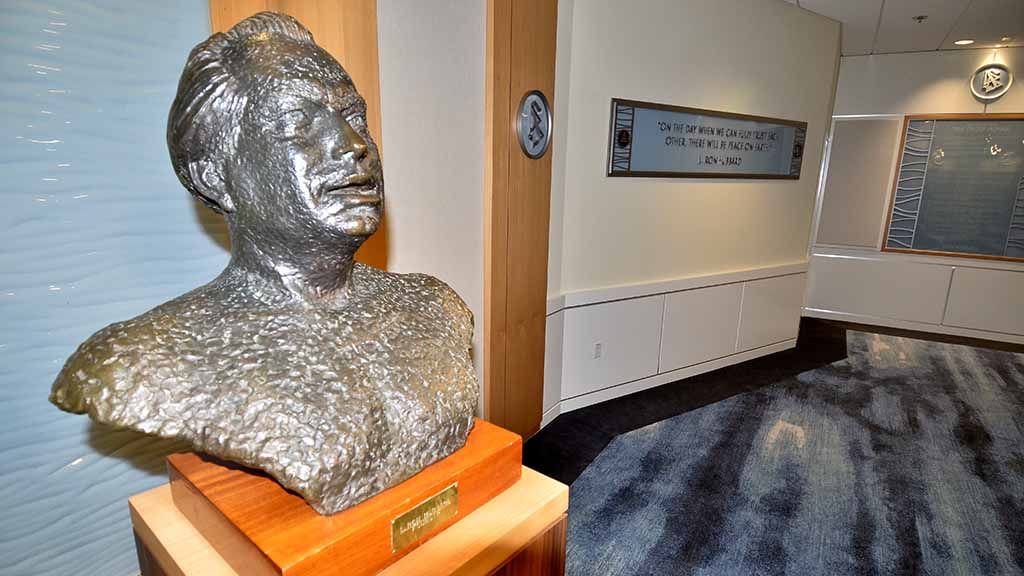 "Bust of L. Ron Hubbard and a wall quote: ""On the day we can fully trust each other, there will be peace on earth."""