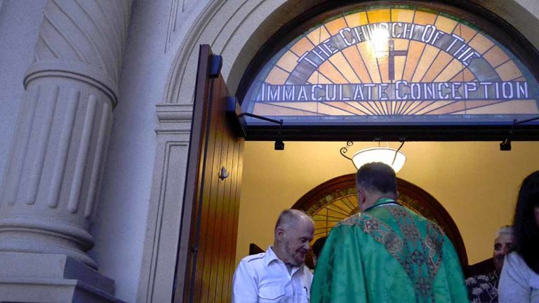 The Rev. Richard Perozich, pastor of Immaculate Conception Catholic Church, greets congregants after Mass. Photo by Chris Stone
