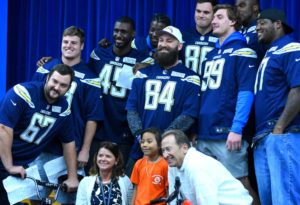 Principal Kathleen Gallagher, Bill Pollakov and Chargers players pose with a girl who won a bike. Photo by Chris Stone