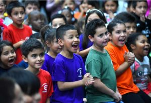 Children dance and squeal with excitement upon the news that they all got a bike. Photo by Chris Stone