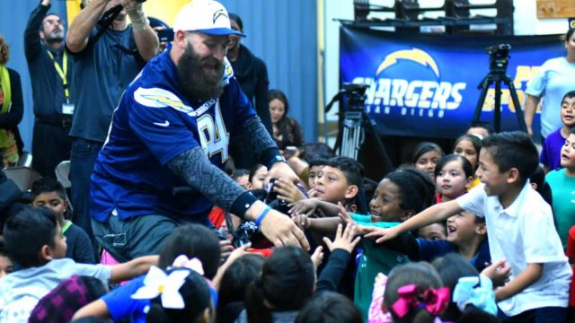 Chargers player Sean McGrath is surrounded by squealing children as he rides in on a bike. Photo by Chris Stone