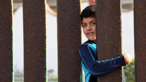 Ignacio, 10, peers from the Mexican side of the border fence before La Posada. Photo by Chris Stone