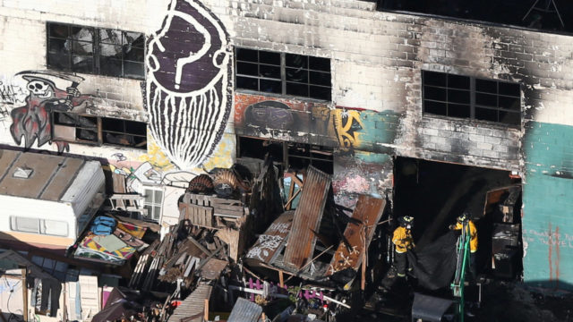 Firefighters work inside the burned warehouse following the fatal fire in the Fruitvale district of Oakland. REUTERS/Lucy Nicholson
