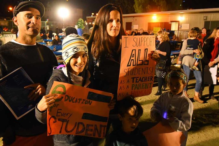 Teachers Doug and Catherine Gilbert of Solana Beach brought signs — and their kids London, 11, Lila, 6, and Sol, 4. Photo by Ken Stone