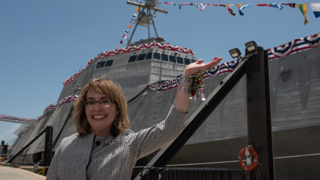 "Former U.S. Rep. Gabrielle ""Gabby"" Giffords waves to a crowd in front of the littoral combat ship  named in her honor. Navy photo"