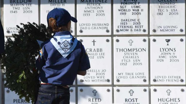 A cub scout with a wreath pauses to read the names of military members buried at Fort Rosecrans National Cemetery. Photo by Chris Stone
