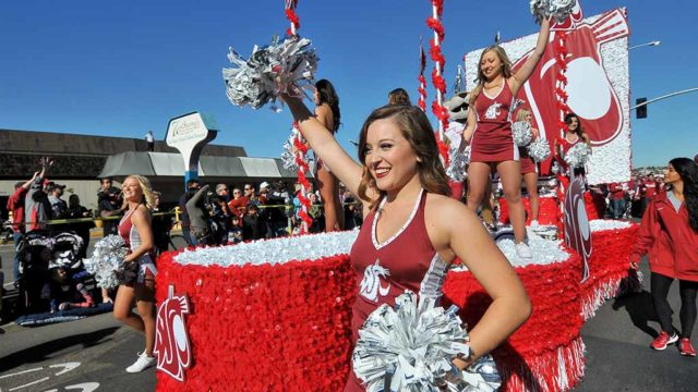 Washington State University cheerleaders accompany Butch T. Cougar, the school mascot on float at Holiday Bowl Parade. Photo by Ken Stone