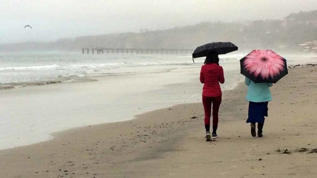 Women walk along La Jolla Shores Beach in the rain. Photo by Chris Stone