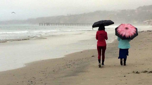 Women walk along La Jolla Shores Beach in the rain. Photo by Chris Stone