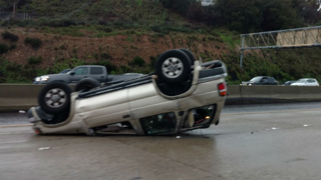 A car involved in a rollover accident on rain-slicked Route 163 in Mission Valley. Photo by Chris Jennewein