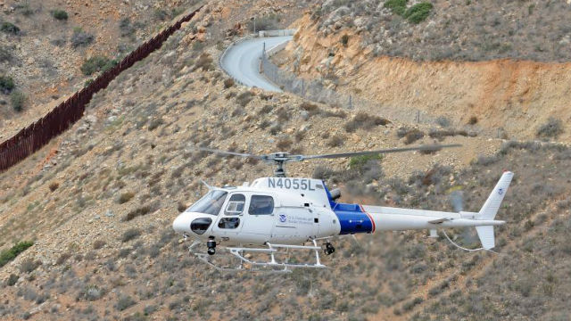 A Customs and Border Patrol helicopter flies along the border near San Diego. Courtesy CBP