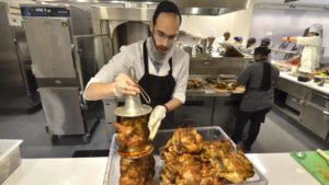 Employee Levy Ceitlin removes cooked Kosher chicken from a bell rotisserie for dining hall's premiere at UCSD. Photo by Chris Stone