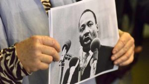 Members of the march coalition held pictures of Martin Luther King Jr. throughout press conference. Photo by Ken Stone