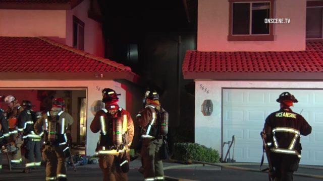 Firefighters outside the burned condominium in Oceanside. Courtesy OnScene.TV