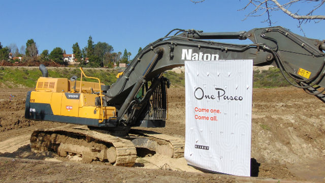 A bulldozer supports a One Paseo sign at the groundbreaking. Photo by Chris Jennewein
